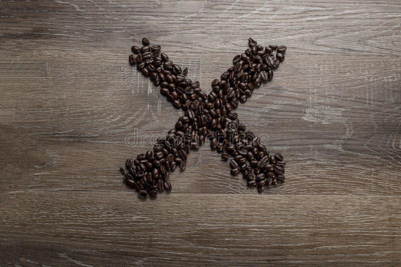 Les grains de café ont arrangé comme lettre X image libre de droits