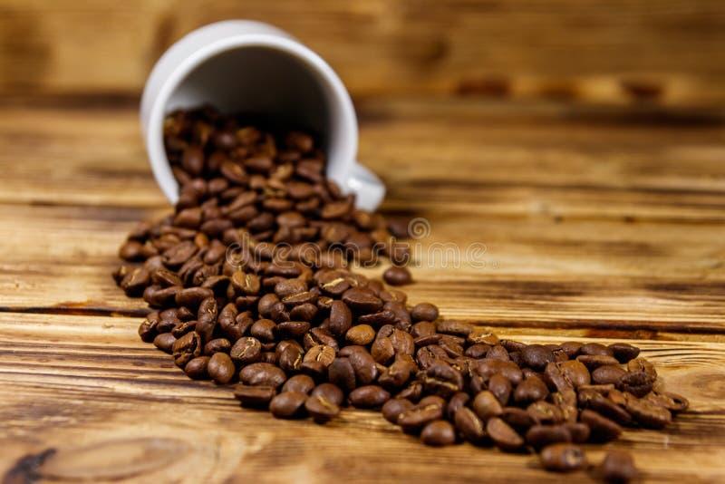 Les grains de café rôtis se renversent hors de la tasse sur la table en bois images libres de droits