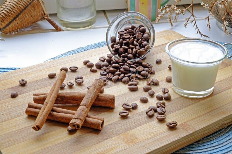 Les grains de café traient et les bâtons de cannelle aménagent le côté en parc photo stock