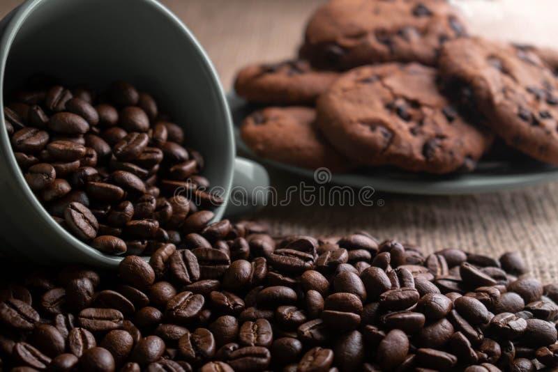 Les grains de caf? se sont ?miett?s avec une tasse, ? l'arri?re-plan un plat des biscuits photos libres de droits