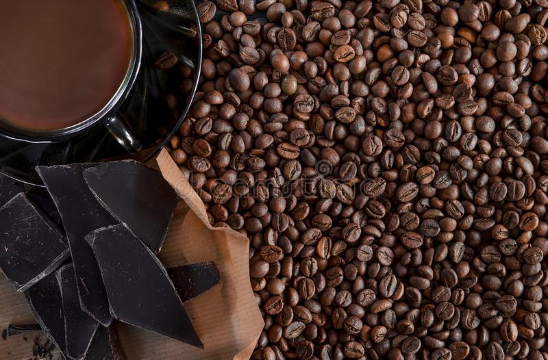 Les grains parfumés rôtis du café noir sont dispersés sur une table en bois noire et il y a une tasse en verre brune avec photos stock