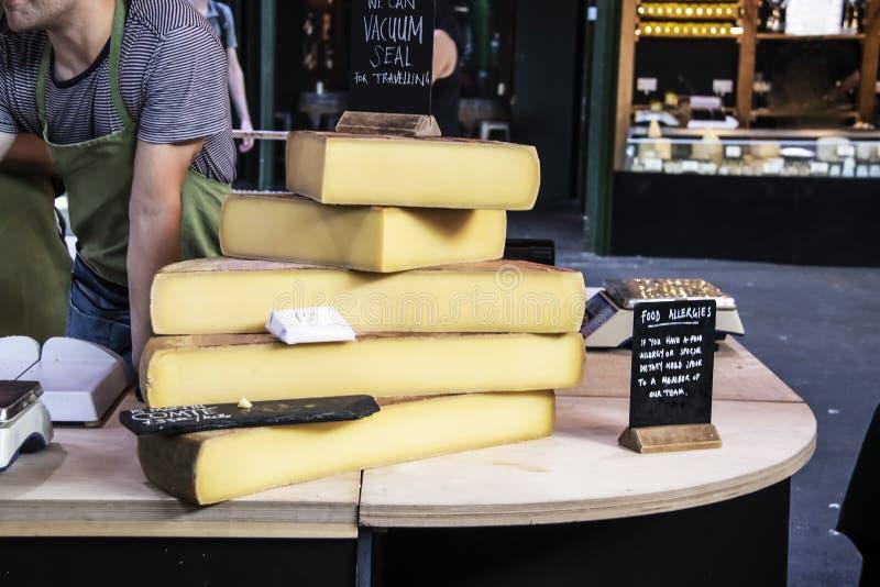 Les grandes dalles du fromage sur la table en bois à un marché avec le travailleur se penchant au-dessus de parler au client et l image libre de droits