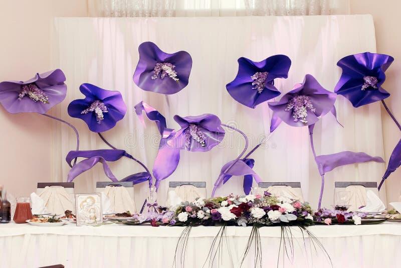 Les grandes fleurs pourpres à la pièce maîtresse de mariage pour la jeune mariée toilettent le settin photos libres de droits