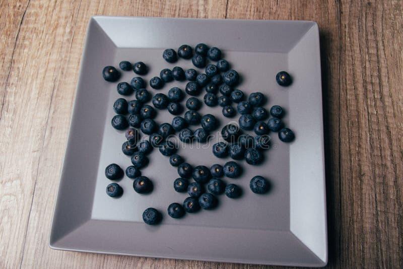 Les grandes, fraîches myrtilles se trouvent d'un plat gris, plan rapproché photographie stock
