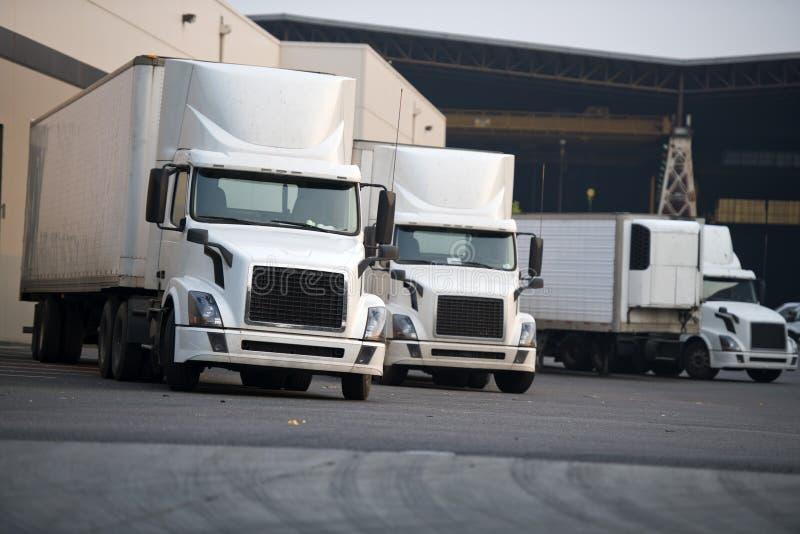 Les grandes installations blanches troque semi la cargaison de chargement sur le parking d'entrepôt image stock