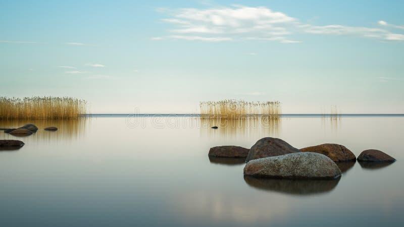 Les grandes roches et le ciel bleu est lac reflété Ladoga le soir images libres de droits