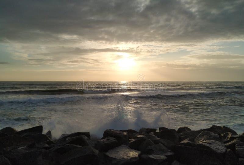 Les grandes vagues éclaboussent au-dessus des roches sur la plage au coucher du soleil des nuages déprimés foncés photos libres de droits