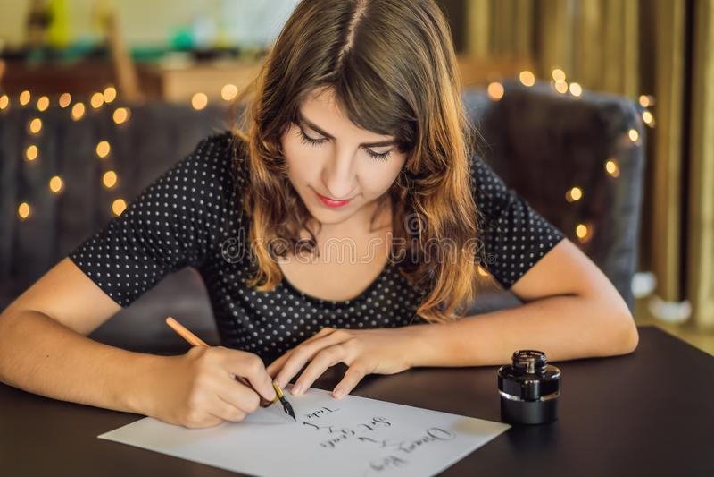 Les grands buts r?veurs d'ensemble agissent Le calligraphe Young Woman ?crit l'expression sur le livre blanc Inscrivant ornementa photos stock