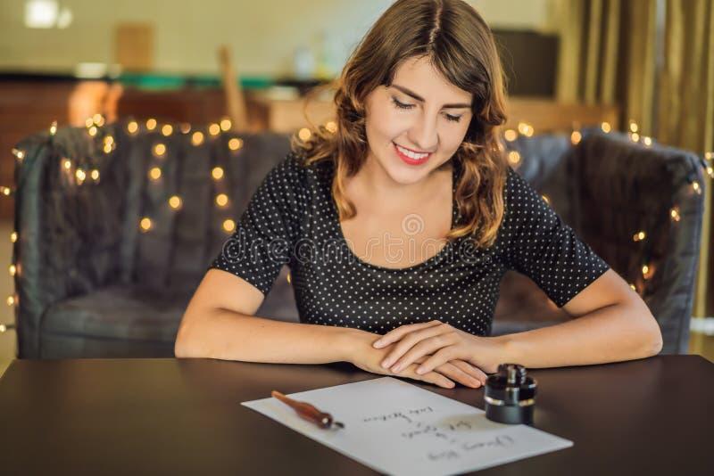 Les grands buts r?veurs d'ensemble agissent Le calligraphe Young Woman ?crit l'expression sur le livre blanc Inscrivant ornementa photo libre de droits