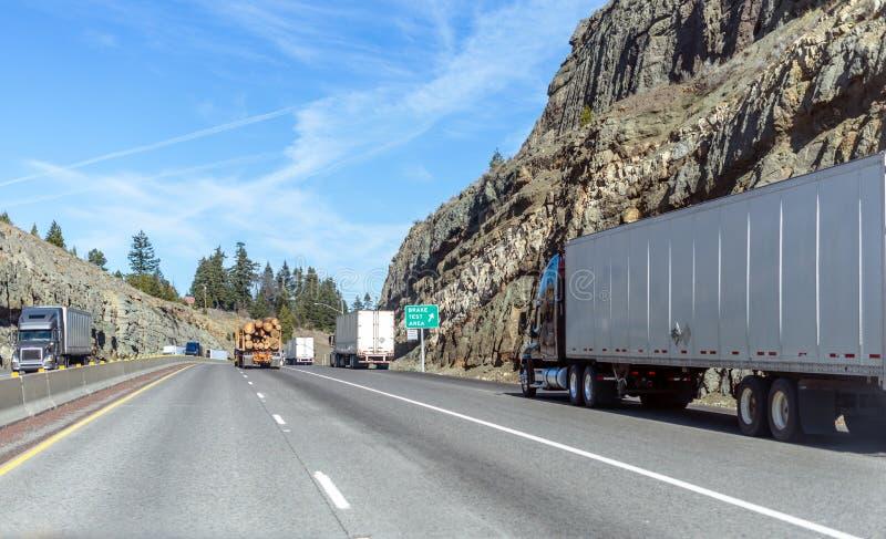 Les grands camions d'installations semi avec charg?es semi les remorques fonctionnant sur le passage de montagne se d?placent le  image libre de droits
