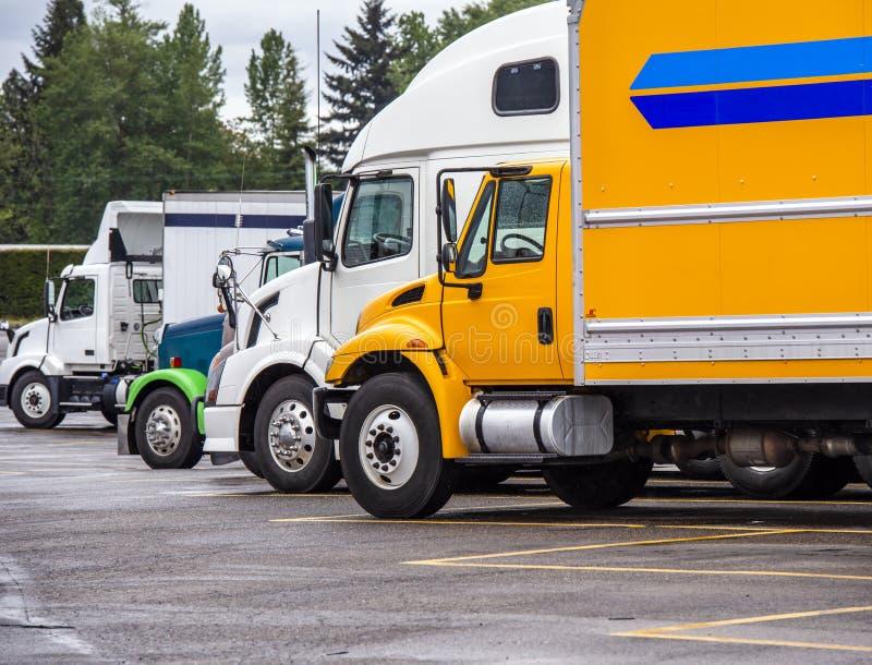 Les grands camions d'installations semi différents fait et classe la position dans la rangée sur le parking de relais routier photo stock
