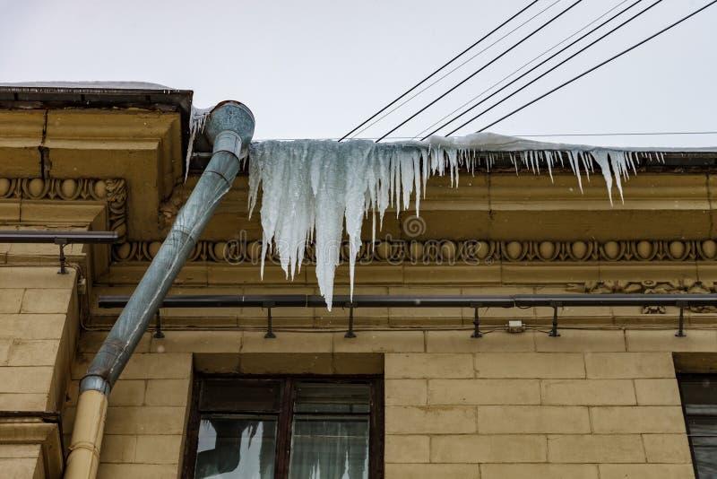 Les grands glaçons accrochent dangereusement sur le toit à côté du drain image libre de droits