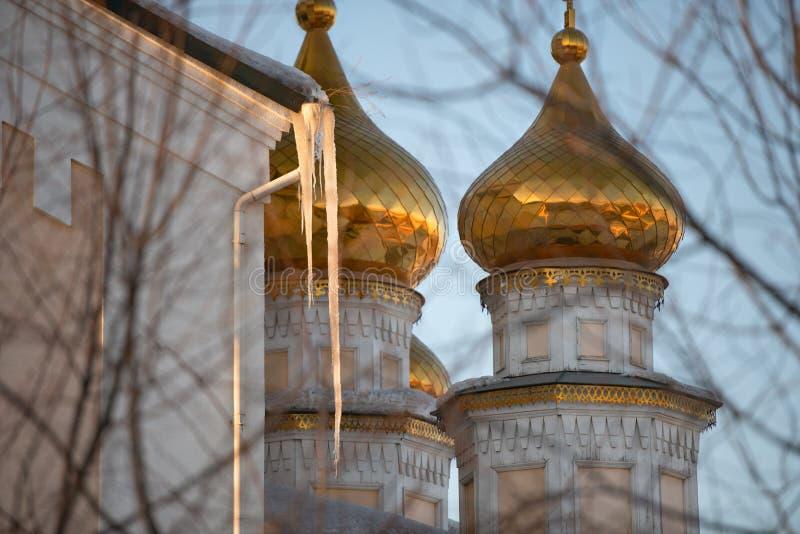 Les grands glaçons pendent du toit sur le fond des dômes d'or de l'église chrétienne à un coucher du soleil photographie stock