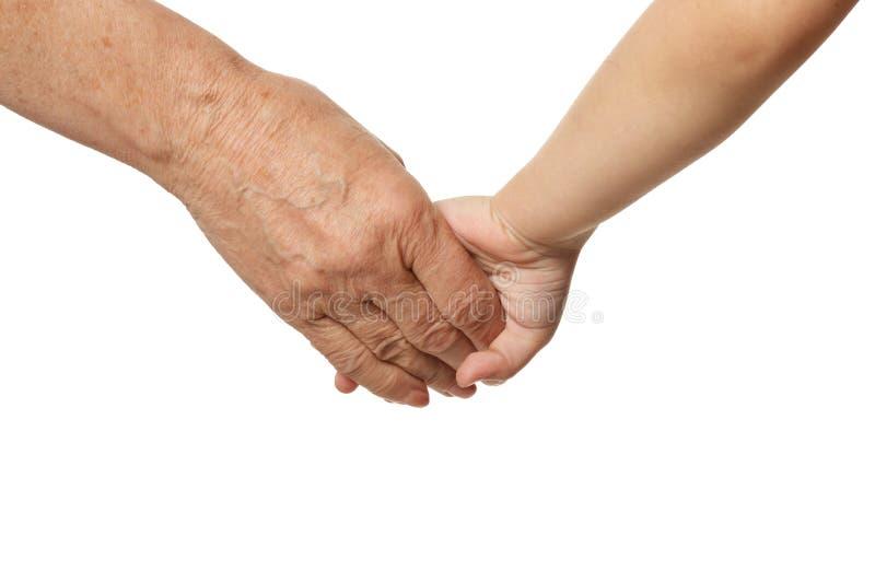 Les grands-mères remettent avec la main de petite fille sur le fond blanc images libres de droits
