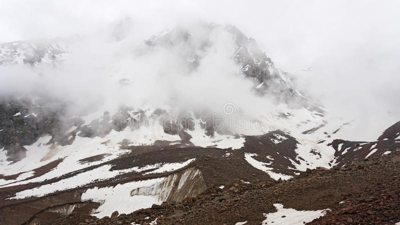 Les grands nuages nagent par la gorge Zone montagneuse La neige est évidente sur les pentes de montagne image stock