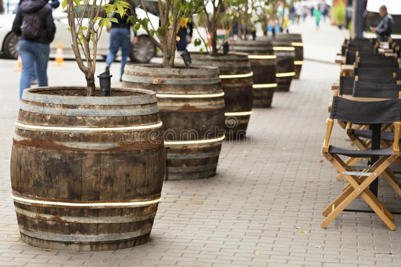 Les grands vieux barils en bois se tiennent le long du café de rue photos stock