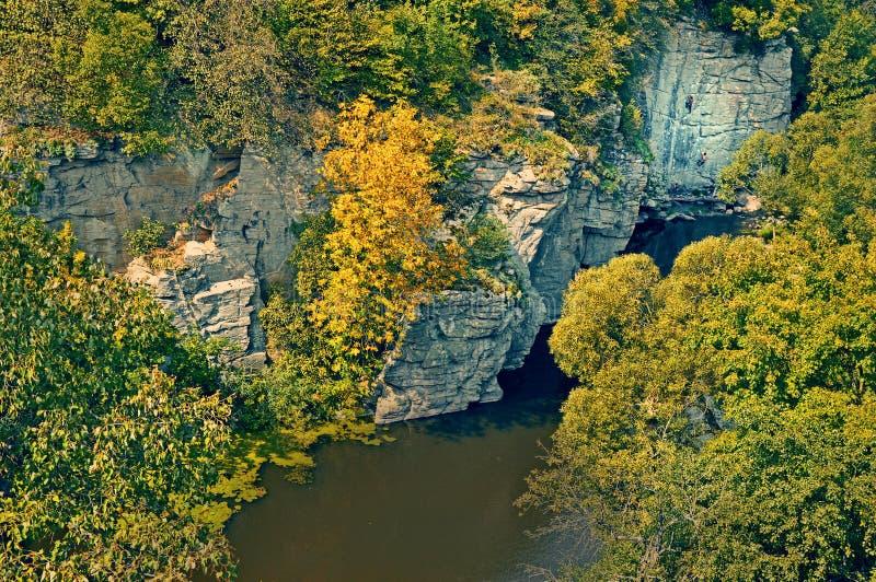 Les grimpeurs montent la corde sur la falaise près de la rivière photographie stock libre de droits