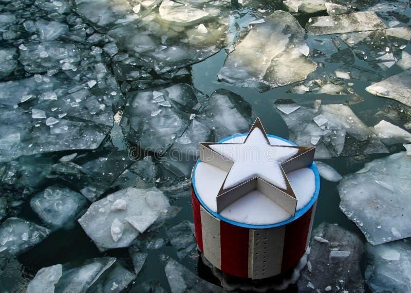 Les gros morceaux de glace flottent en rivière Chicago congelée à côté d'un briseur de vague patriotique photo libre de droits