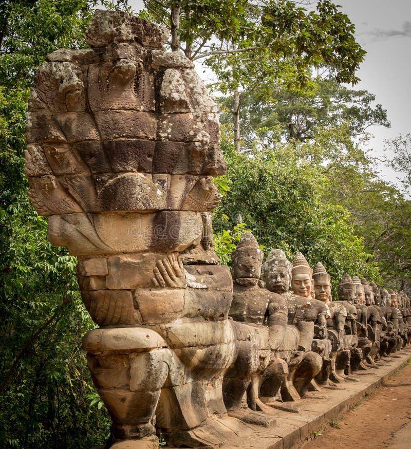 Les guerriers rayent l'entrée au thom du sud d'angkor de porte images stock