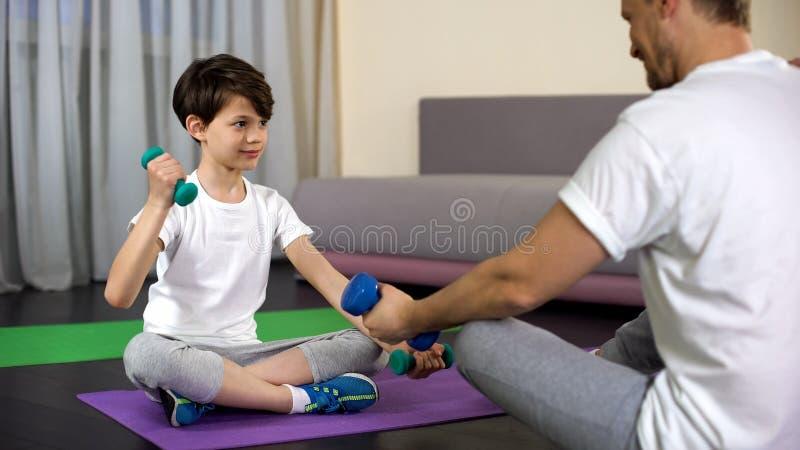 Les haltères de levage de père et de fils, montrant des exercices de forme physique d'enfant, folâtrent la famille images stock