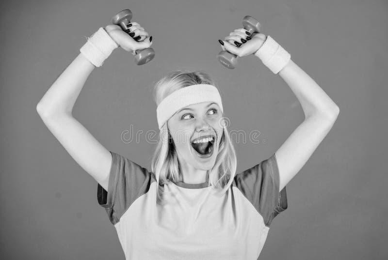 Les halt?res de prise de fille portent des bracelets Concept de sport et de forme physique Femme s'exer?ant avec des halt?res Exe photographie stock libre de droits