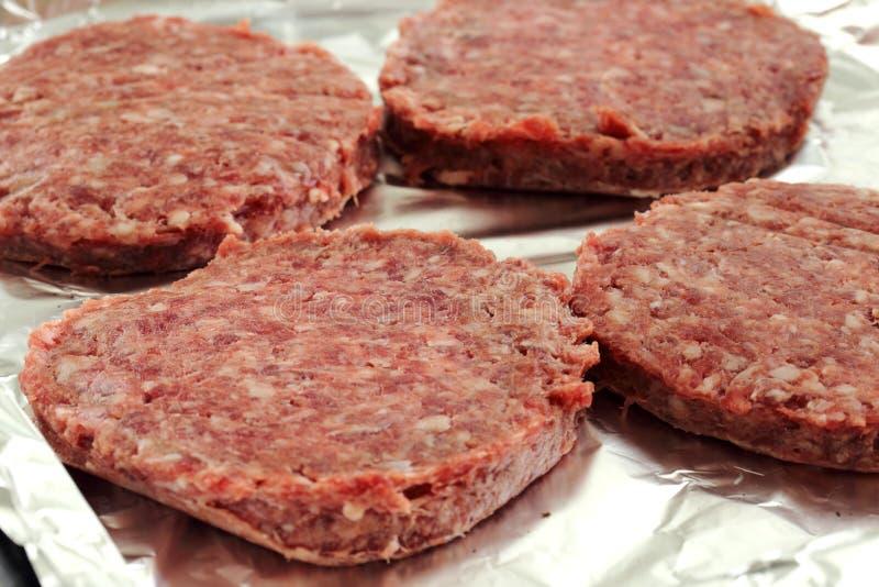 Les hamburgers crus de boeuf sur un aluminium ont couvert le plateau de cuisson photo stock