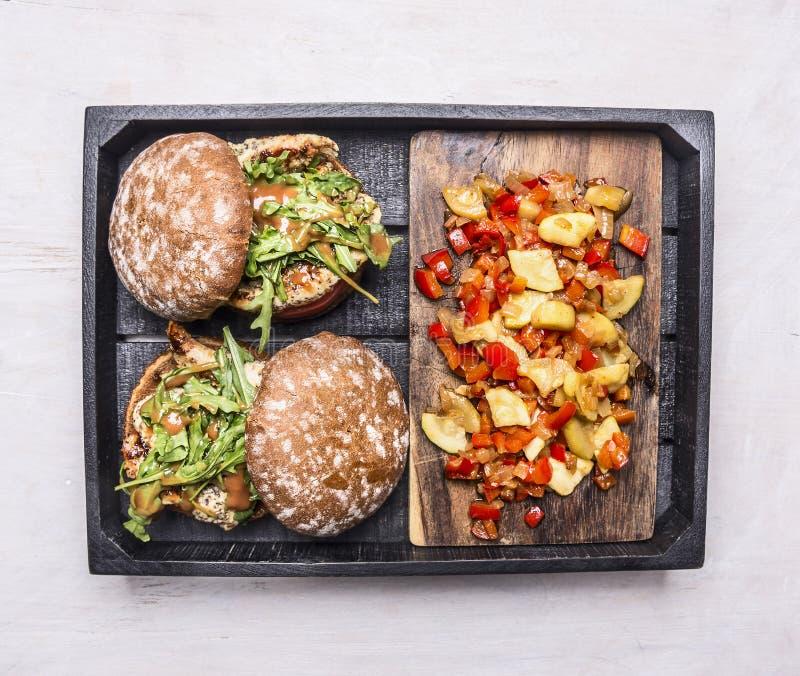 Les hamburgers faits maison avec le poulet en sauce à moutarde avec l'arugula et garnissent de la ratatouille dans une boîte en b photos libres de droits