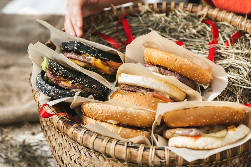 Les hamburgers frais se sont pliés dans le panier en osier, plan rapproché tiré photos stock