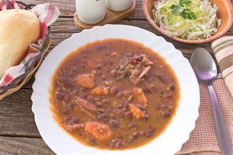 Les haricots cuits au four avec la viande de porc sèche dans le plat avec de la salade ont servi images libres de droits