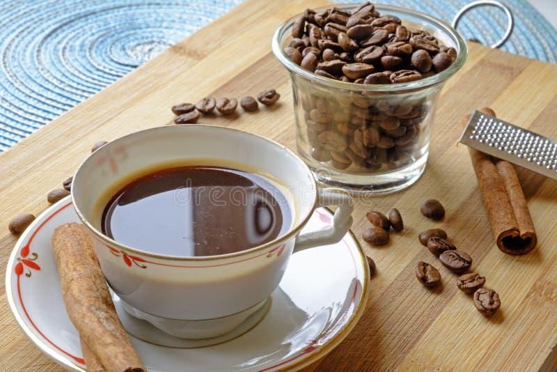 Les haricots de tasse de café et les bâtons de cannelle aménagent la culture en parc latérale images stock