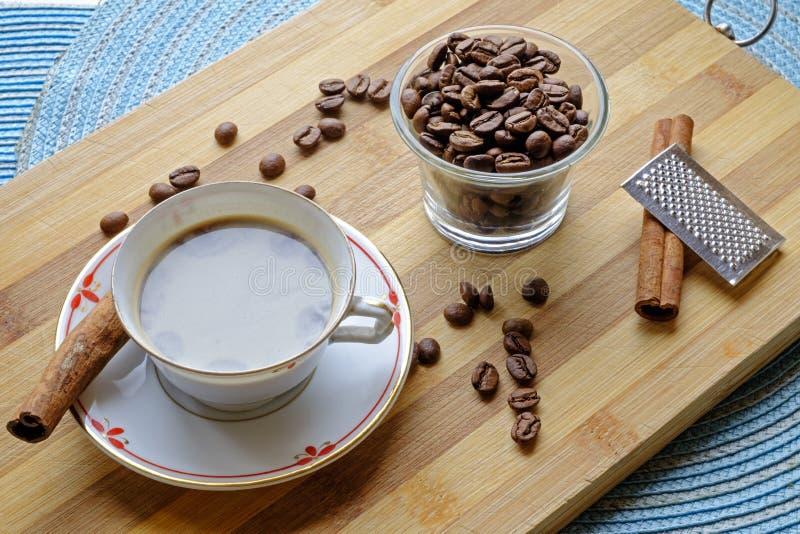 Les haricots de tasse de café et les bâtons de cannelle aménagent le côté en parc photo libre de droits