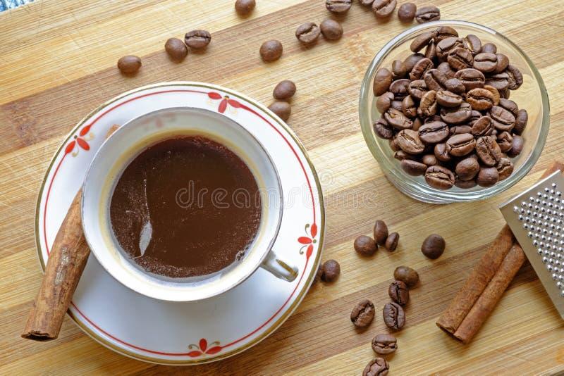 Les haricots de tasse de café et les bâtons de cannelle aménagent serré en parc supérieur photo libre de droits