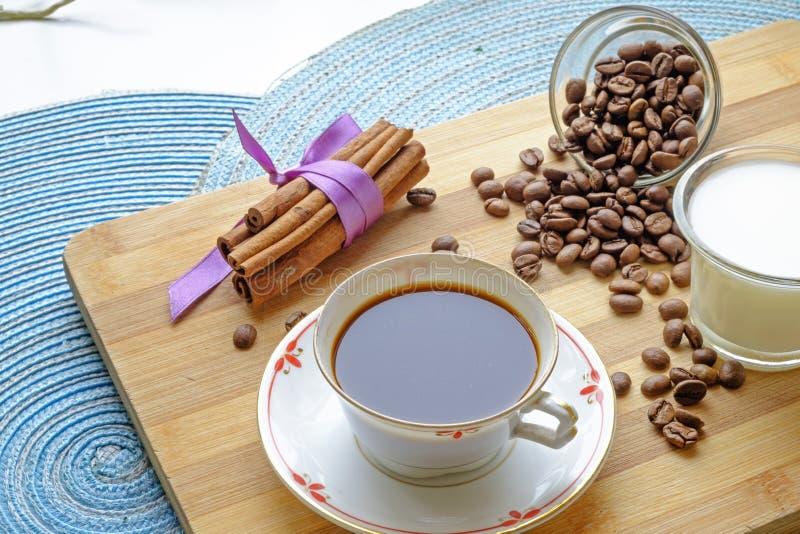 Les haricots de tasse de café traient et les bâtons de cannelle aménagent la culture en parc latérale photographie stock libre de droits