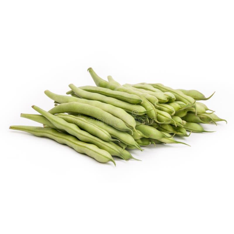 Les haricots verts frais sur la table, blanc ont isolé le fond photographie stock