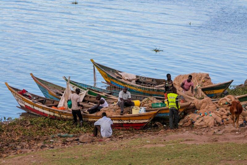 Les hommes africains de pêcheur sur le lac étayent près du bateau préparant le filet pour la pêche image stock