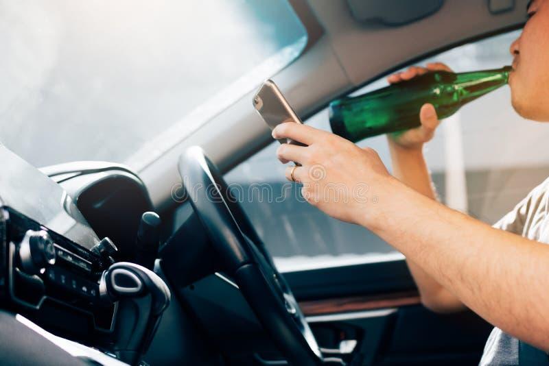Les hommes asiatiques boivent l'alcool dans la voiture et des téléphones portables d'utilisation tout en conduisant image stock