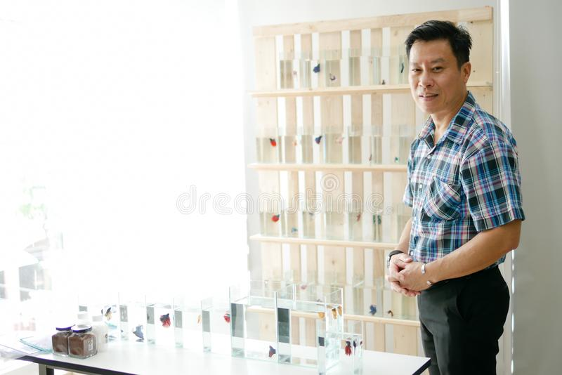 Les hommes asiatiques futés vendant le betta de combat siamois de poissons sont welcom photographie stock