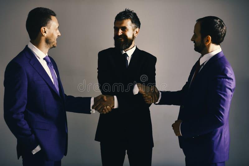 Les hommes avec la barbe et les visages heureux discutent des plans d'action se serrant la main Les hommes d'affaires portent les photographie stock libre de droits