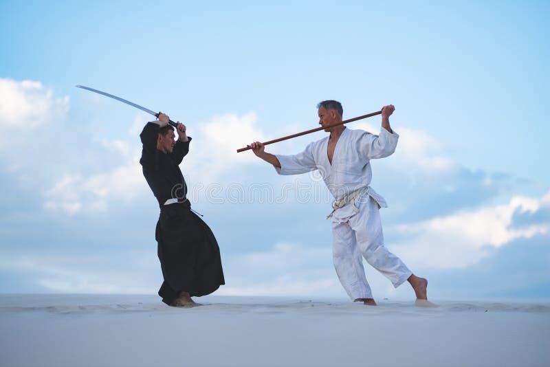 Les hommes concentrés, dans des vêtements japonais, pratiquent des arts martiaux image libre de droits