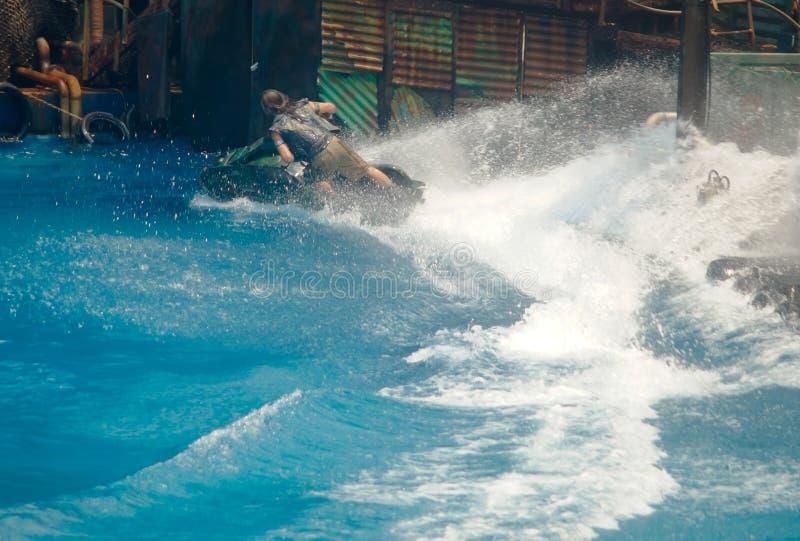 Les hommes conduisant le ski de jet tournent l'action gauche sur l'eau images libres de droits