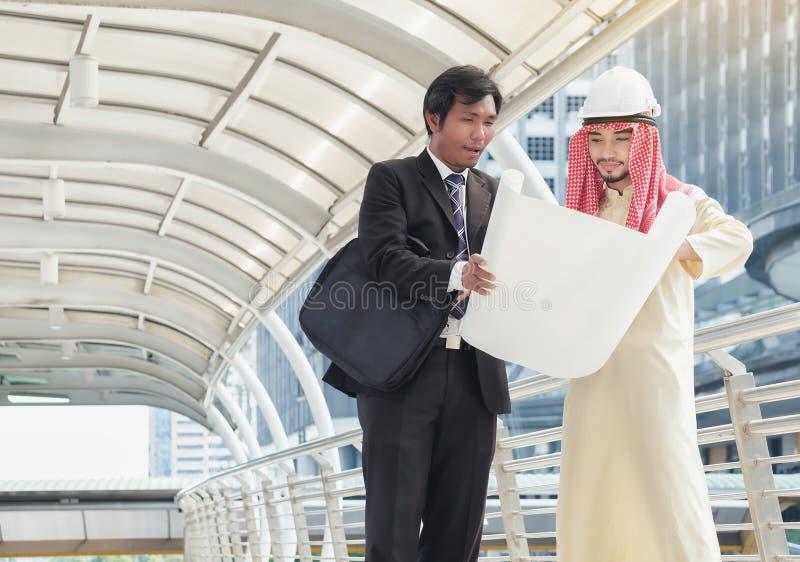 Les hommes d'affaires asiatiques et les architectes arabes ont consulté sur le projet commun photos stock