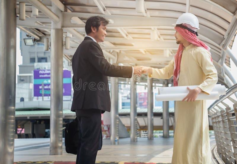 Les hommes d'affaires asiatiques et les architectes arabes ont la poignée de main convenue sur a image libre de droits