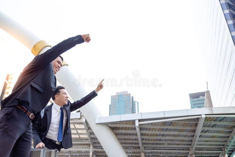 Les hommes d'affaires beaux sont main en hausse  Ils sont une bonne équipe ou photo libre de droits