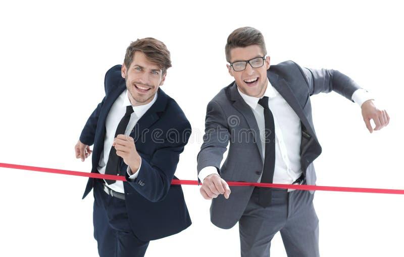 Les hommes d'affaires croisent la ligne d'arrivée photos stock