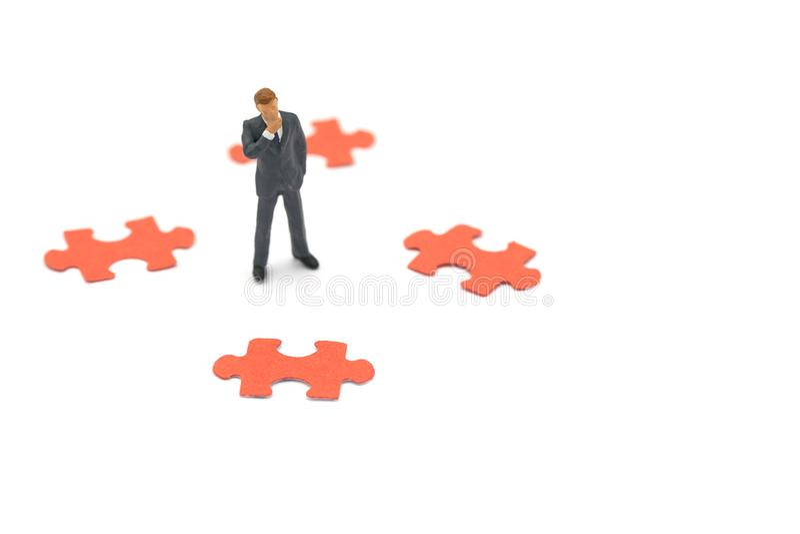 Les hommes d'affaires miniatures de personnes se tenant avec des puzzles denteux analysent le processus d'affaires, trouvent le p photo libre de droits