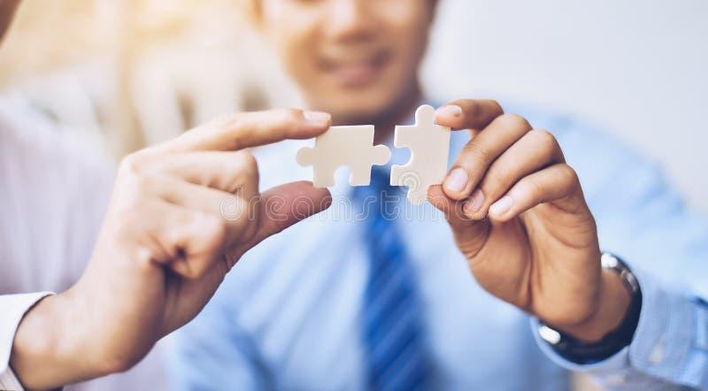 Les hommes d'affaires tiennent des puzzles denteux l'un pour l'autre Teamwor d'affaires photographie stock libre de droits