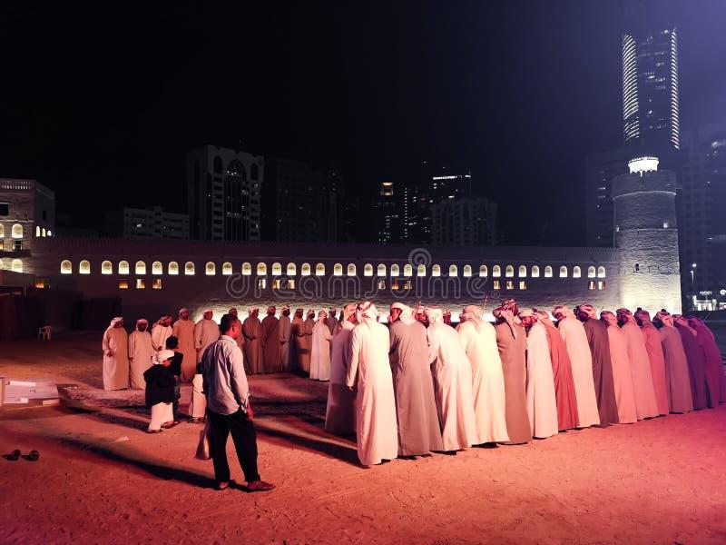 Les hommes d'Emirati exécutent une danse du Moyen-Orient de tradional le Yowla photo stock