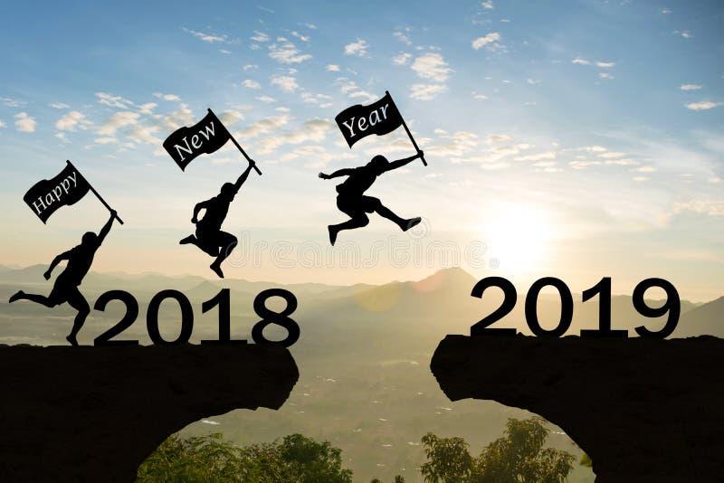 Les hommes de la bonne année 2019 sautent par-dessus des montagnes de silhouette photos stock
