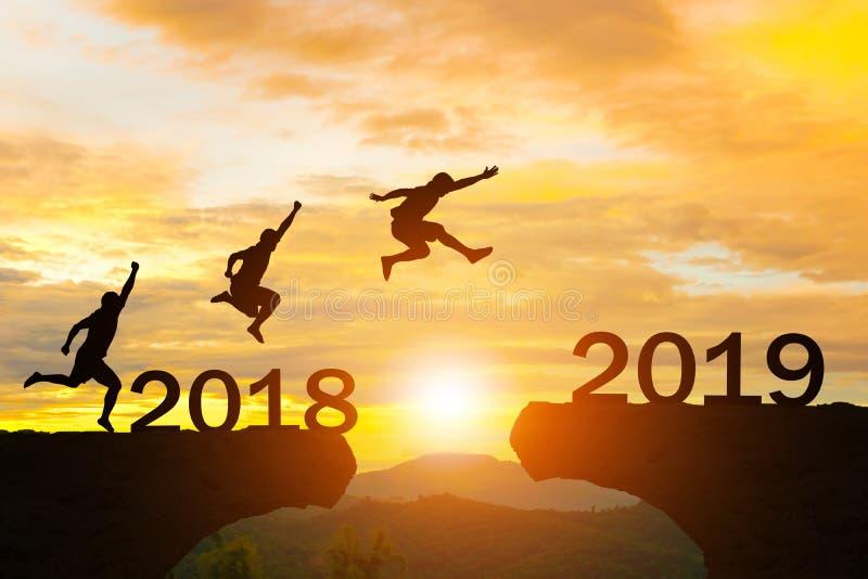 Les hommes de la bonne année 2019 sautent par-dessus la silhouette photos libres de droits