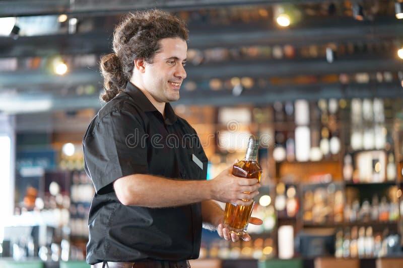 Les hommes de waitre donne une bouteille de whiskey image stock
